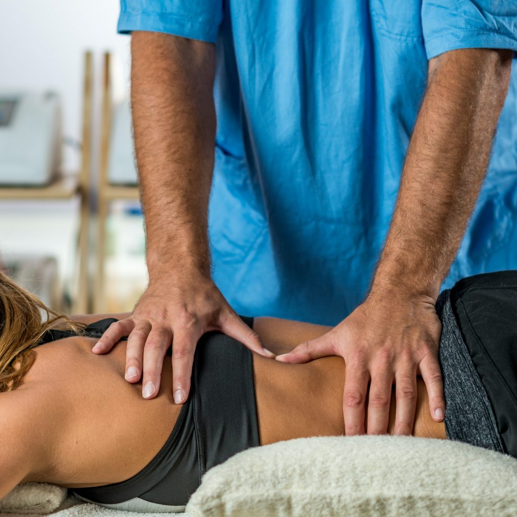 Physical therapy. Therapist applying strong pressure onto lower